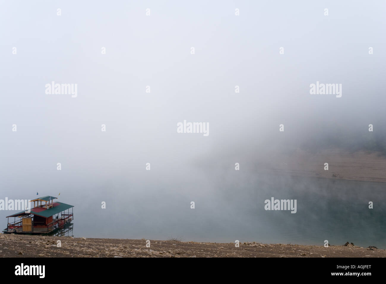 Raft house alone on lake in early morning fog, Lokve in Croatia alpfabet atmospheric Stock Photo