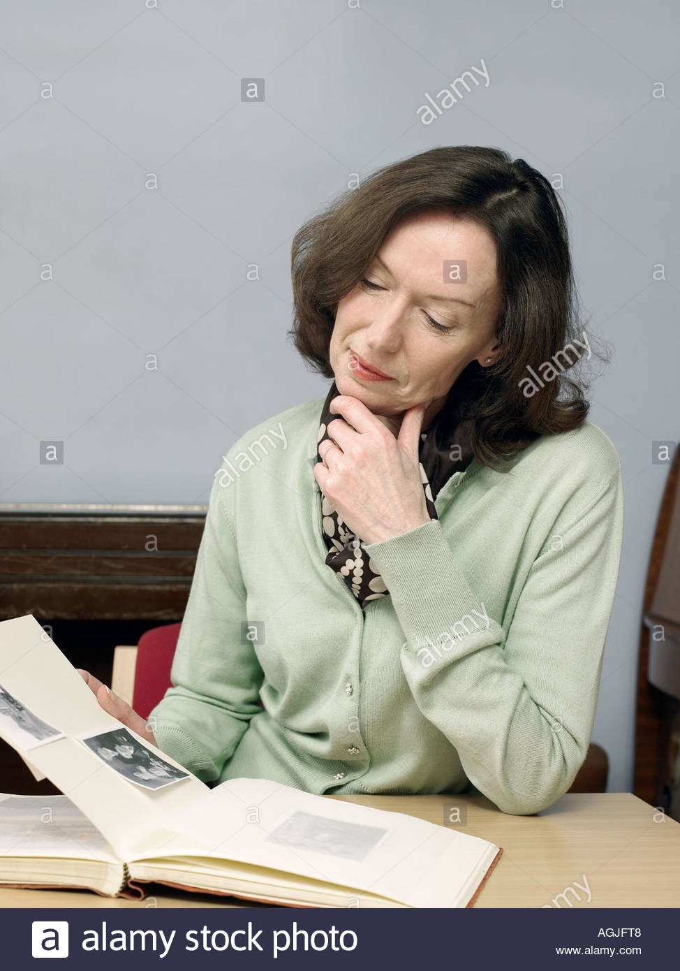 Woman looking at photo album - Stock Image
