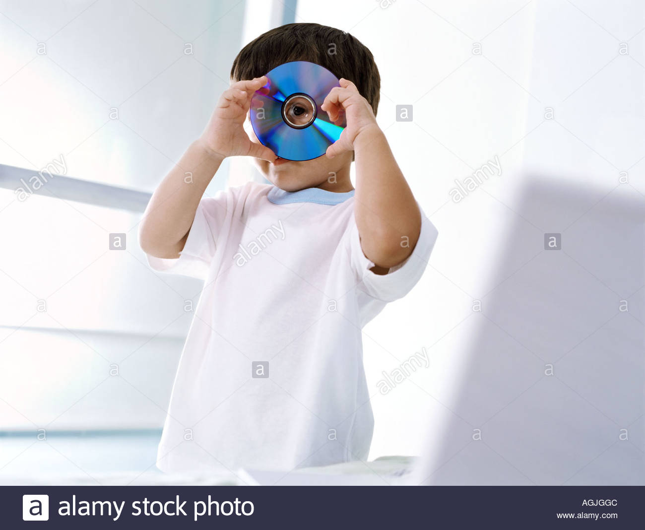 Boy looking through a compact disc - Stock Image