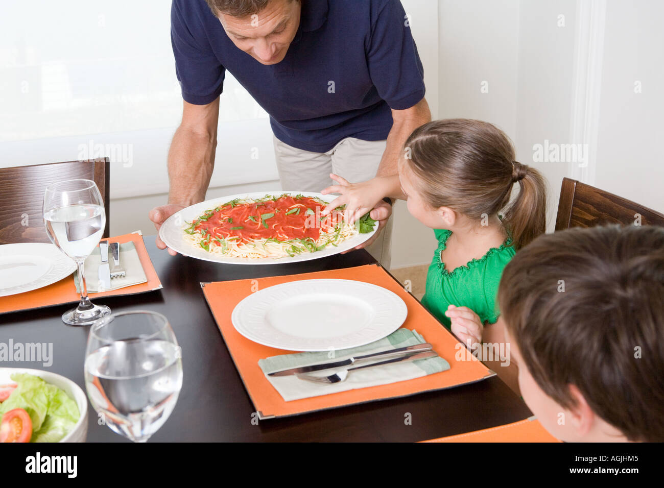 Girl taking spaghetti as father tries to serve meal - Stock Image