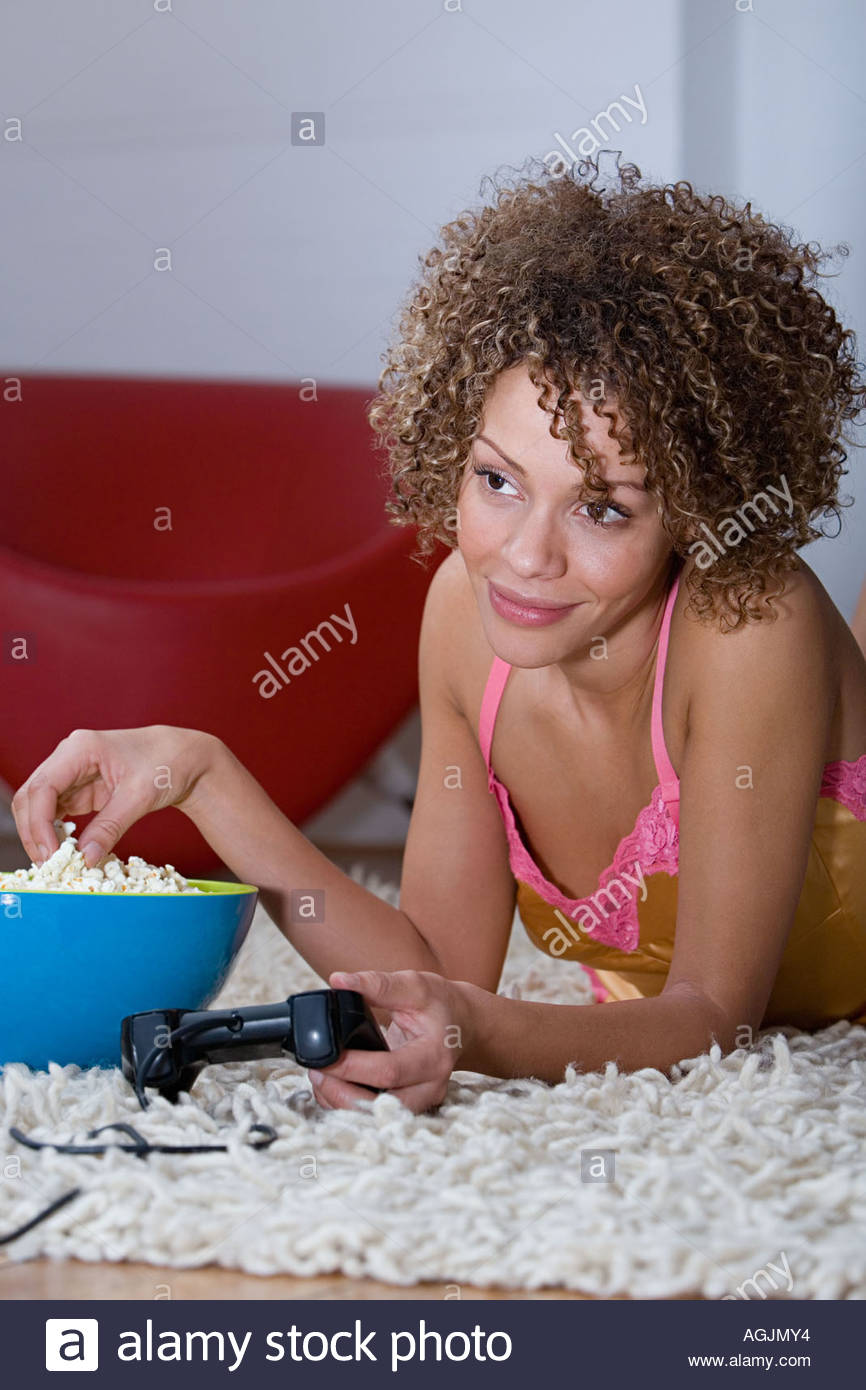 Woman with popcorn and games controller - Stock Image
