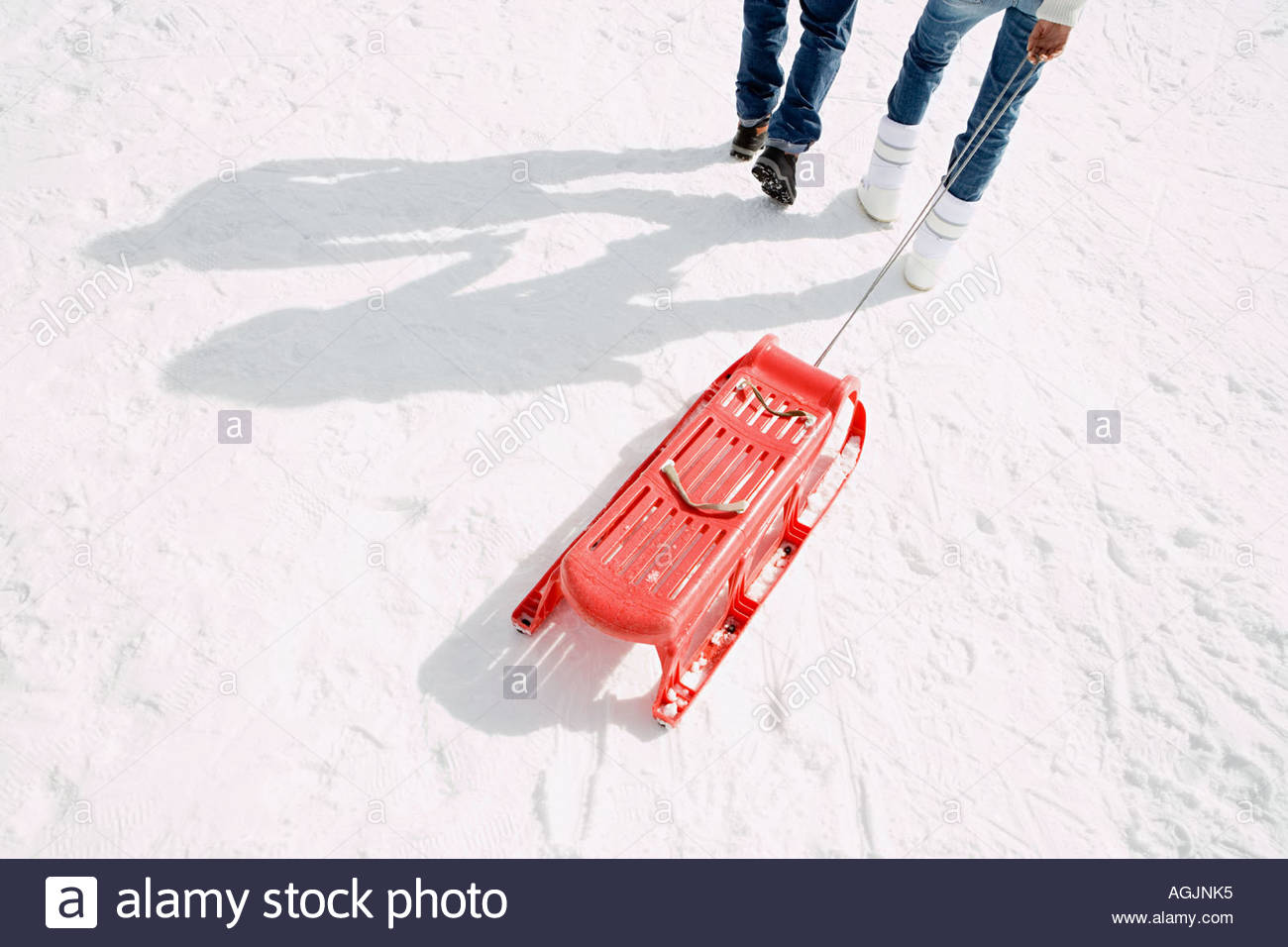 Two people pulling a sleigh - Stock Image