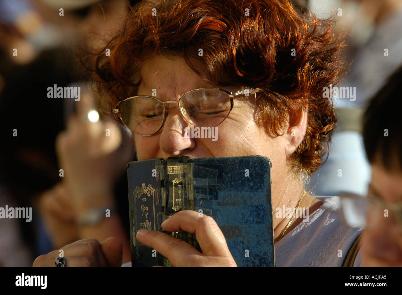 A Jewish worshiper holding a Siddur prayerbook during a prayer at the Western wall or Kotel East Jerusalem Israel - Stock Image