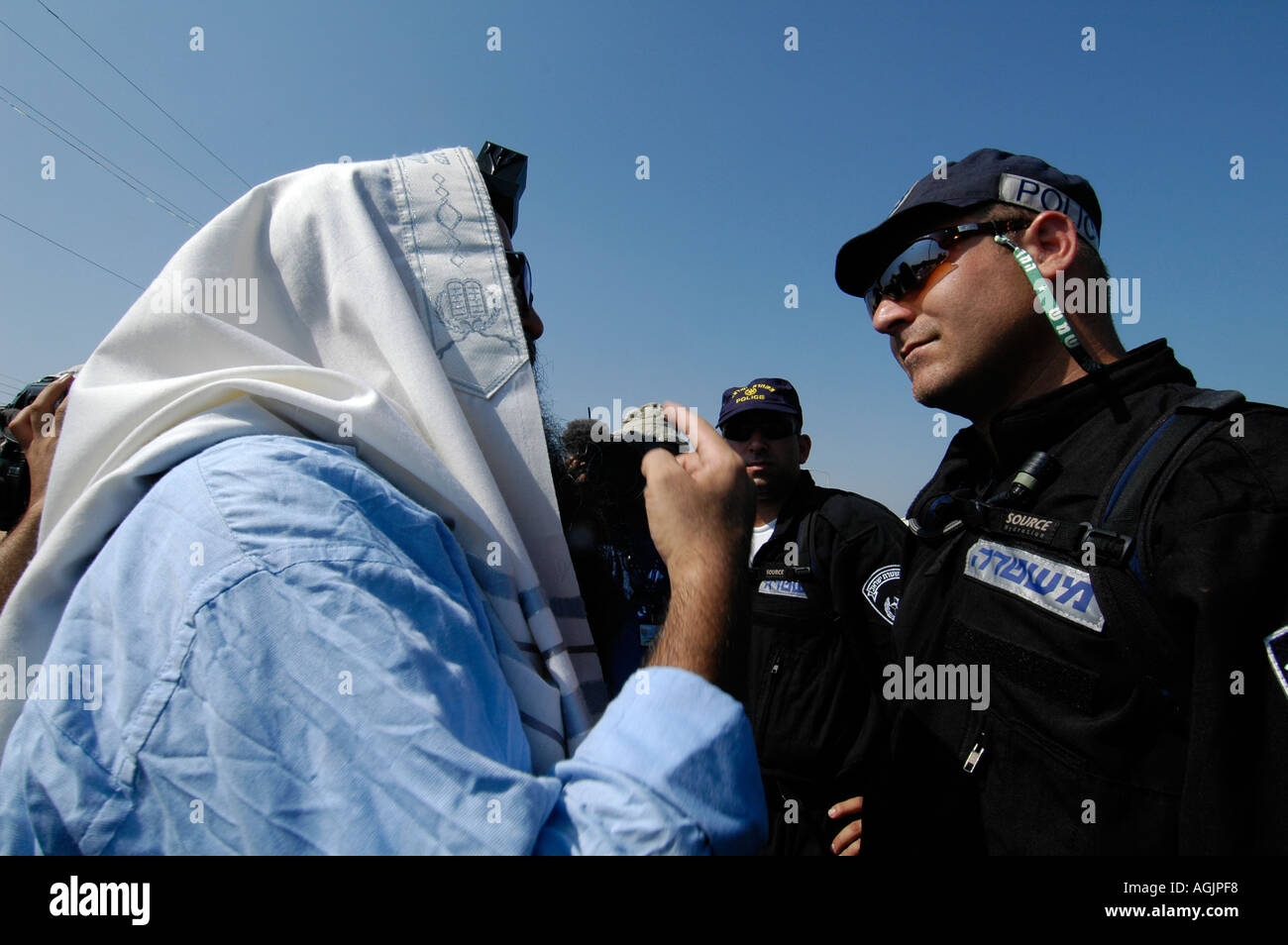 A religious Jewish settler wrapped with a Talit shawl and Tfilin arguing with Israeli policeman during Jewish settlements evacuation from Gaza strip - Stock Image
