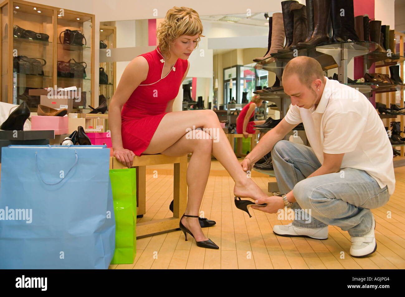 Man helping girlfriend try on shoes - Stock Image