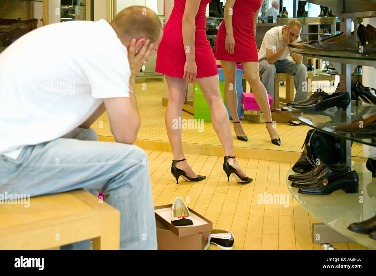 Fed up boyfriend watching woman try on shoes - Stock Image