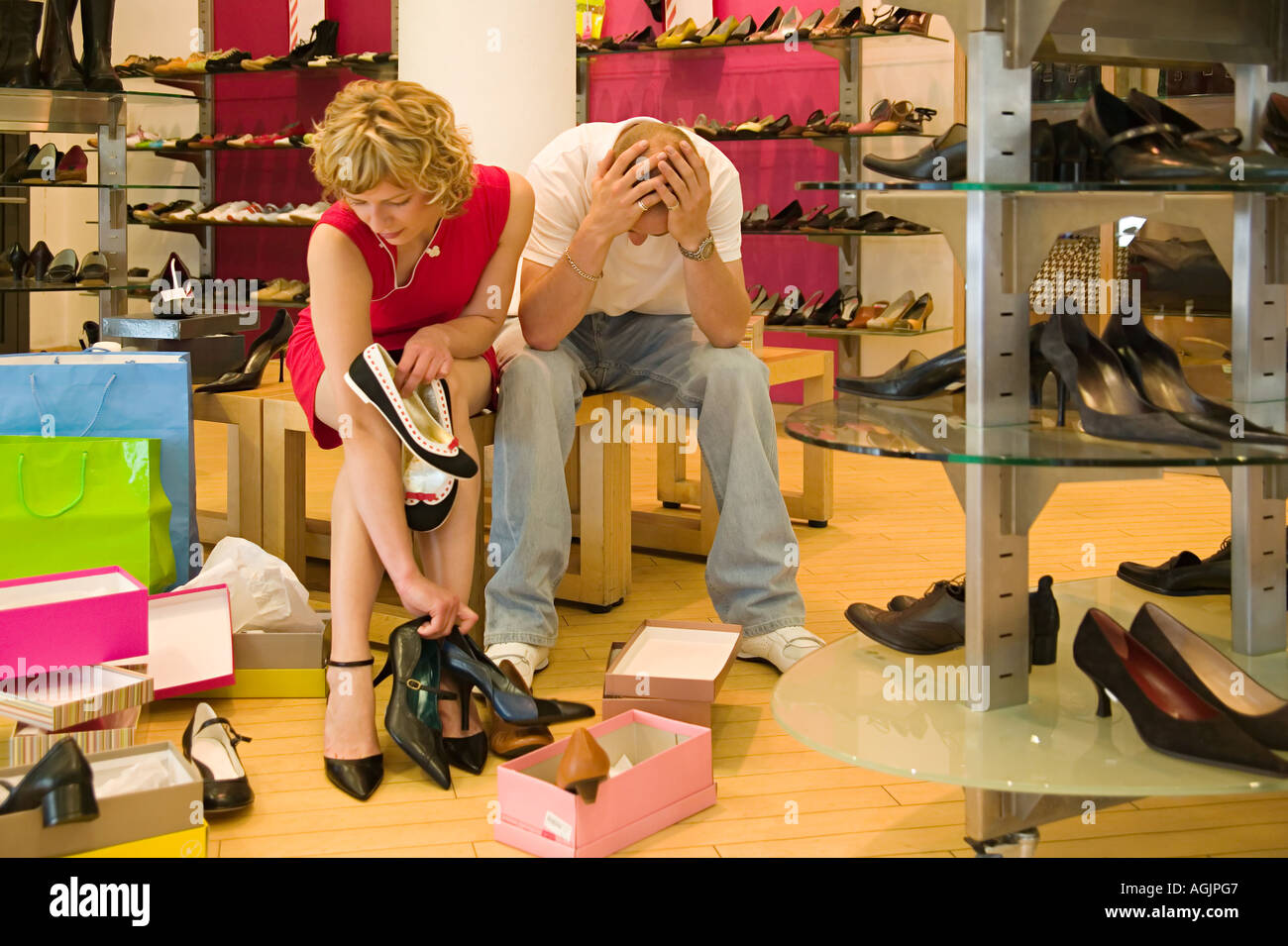 Man despairing as woman chooses shoes - Stock Image