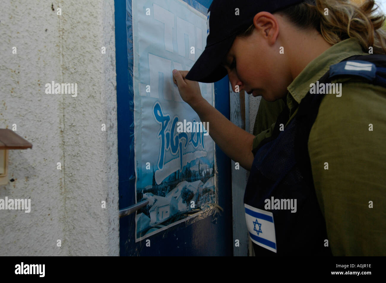 An Israeli female officer knocking on the door of a Jewish settler in Tel Katifa during Jewish settlements evacuation from Gaza strip - Stock Image