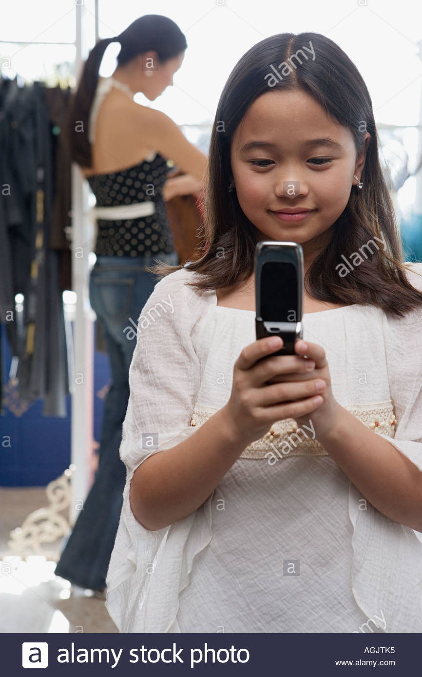 Girl with texting in clothes shop - Stock Image