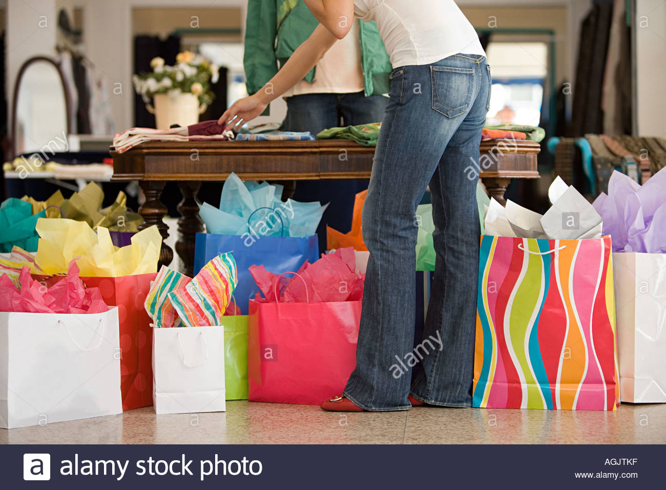 Woman in shop with shopping bags - Stock Image