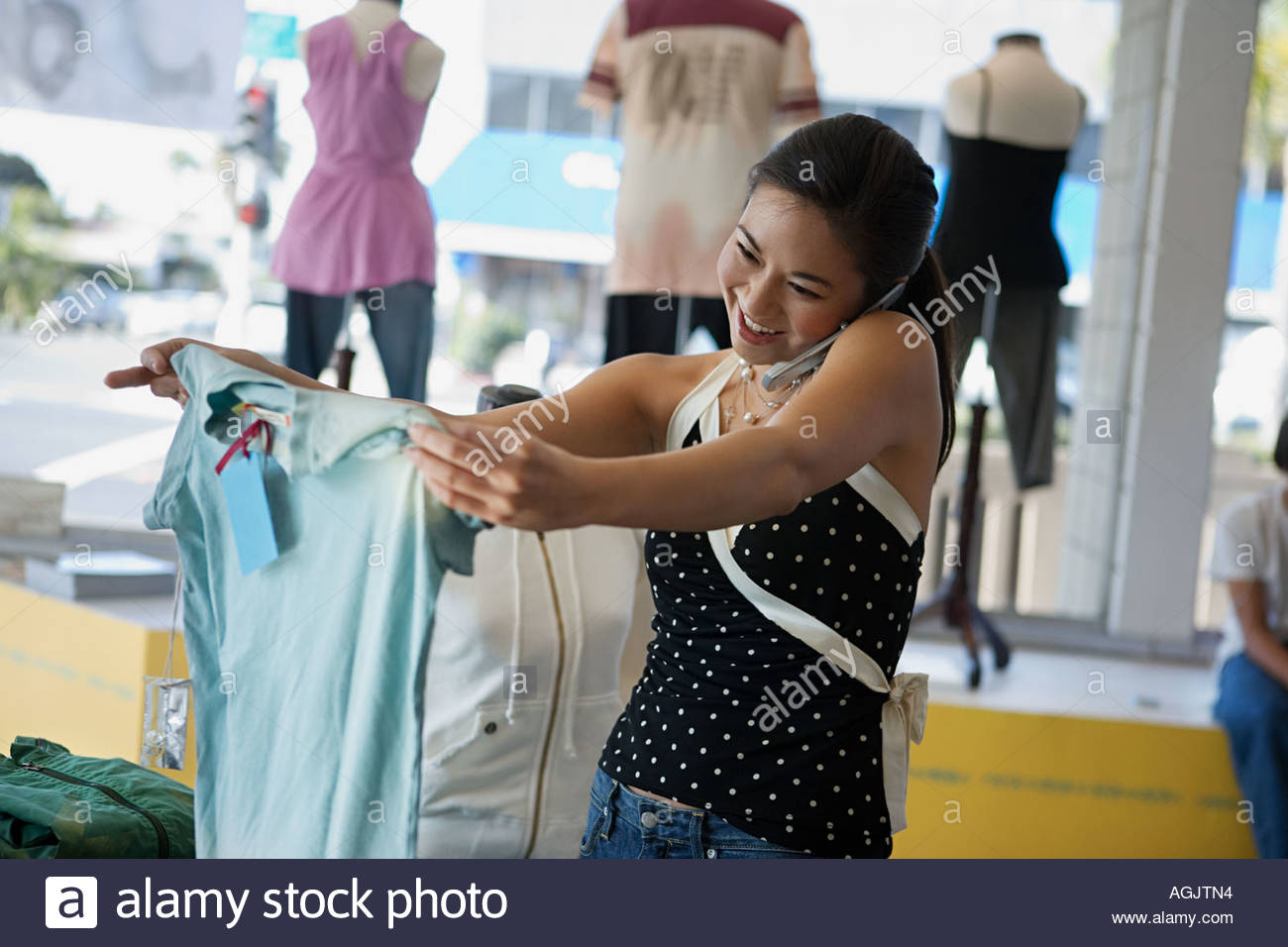 Woman on cellphone in clothes shop - Stock Image