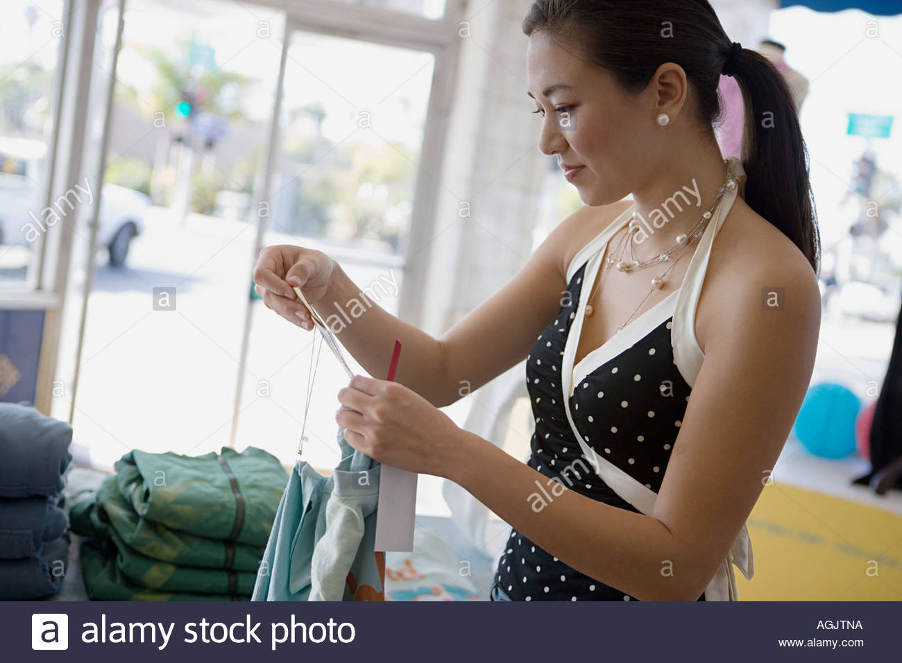 Woman looking at label on clothing - Stock Image
