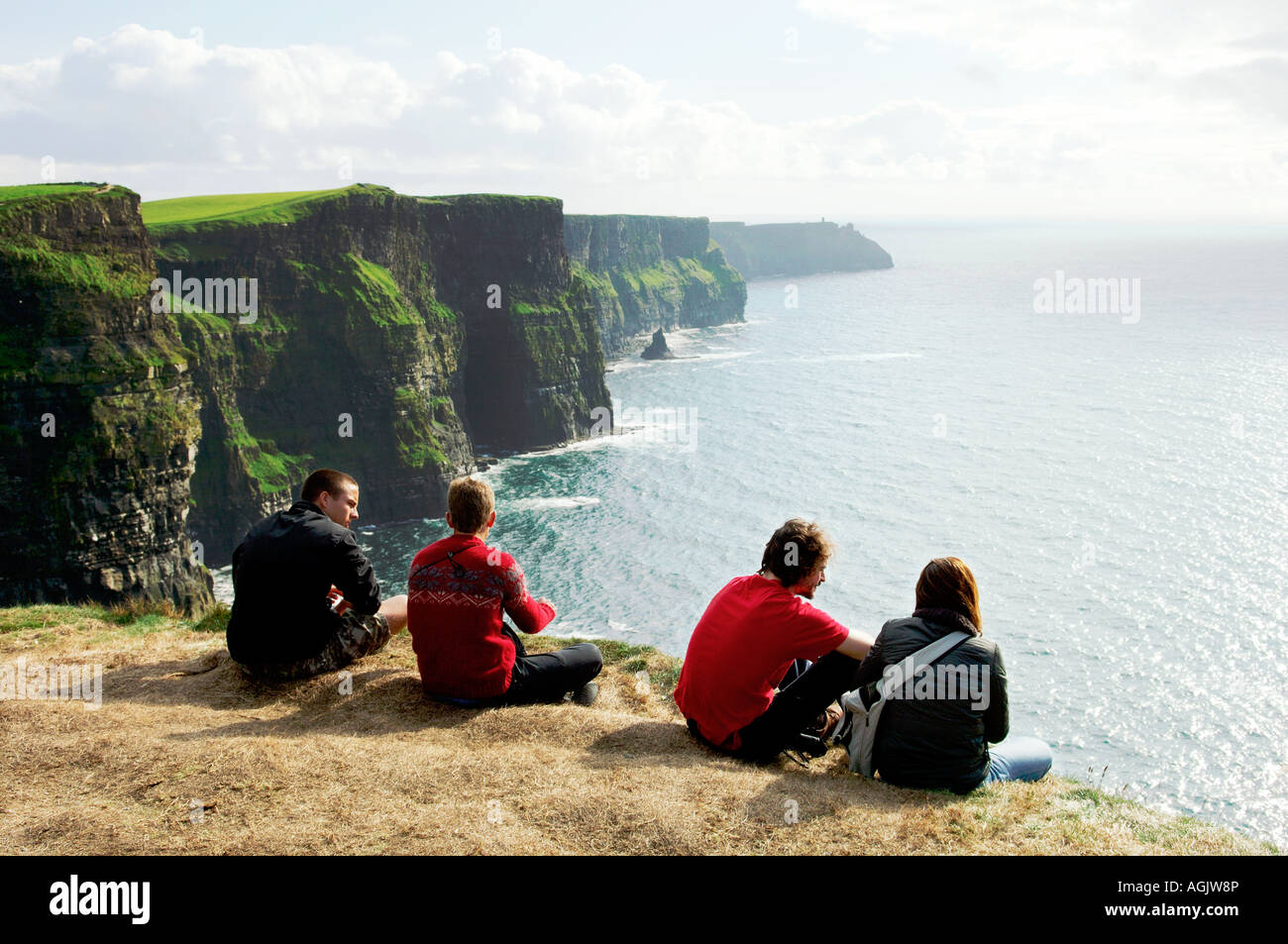 Young people sitting on edge of the Cliffs of Moher in County Clare west Ireland - Stock Image