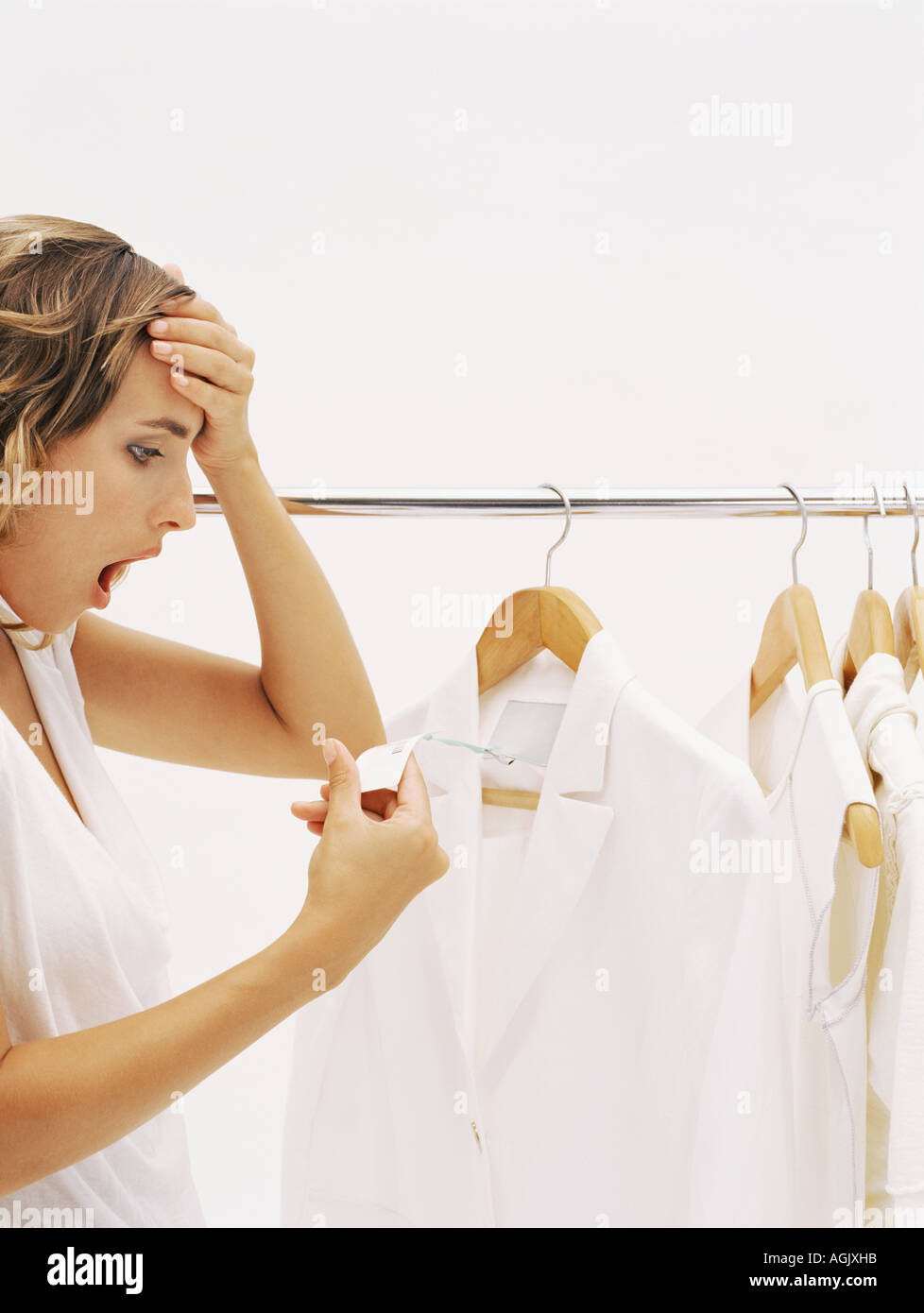Woman shocked at price in clothes shop - Stock Image