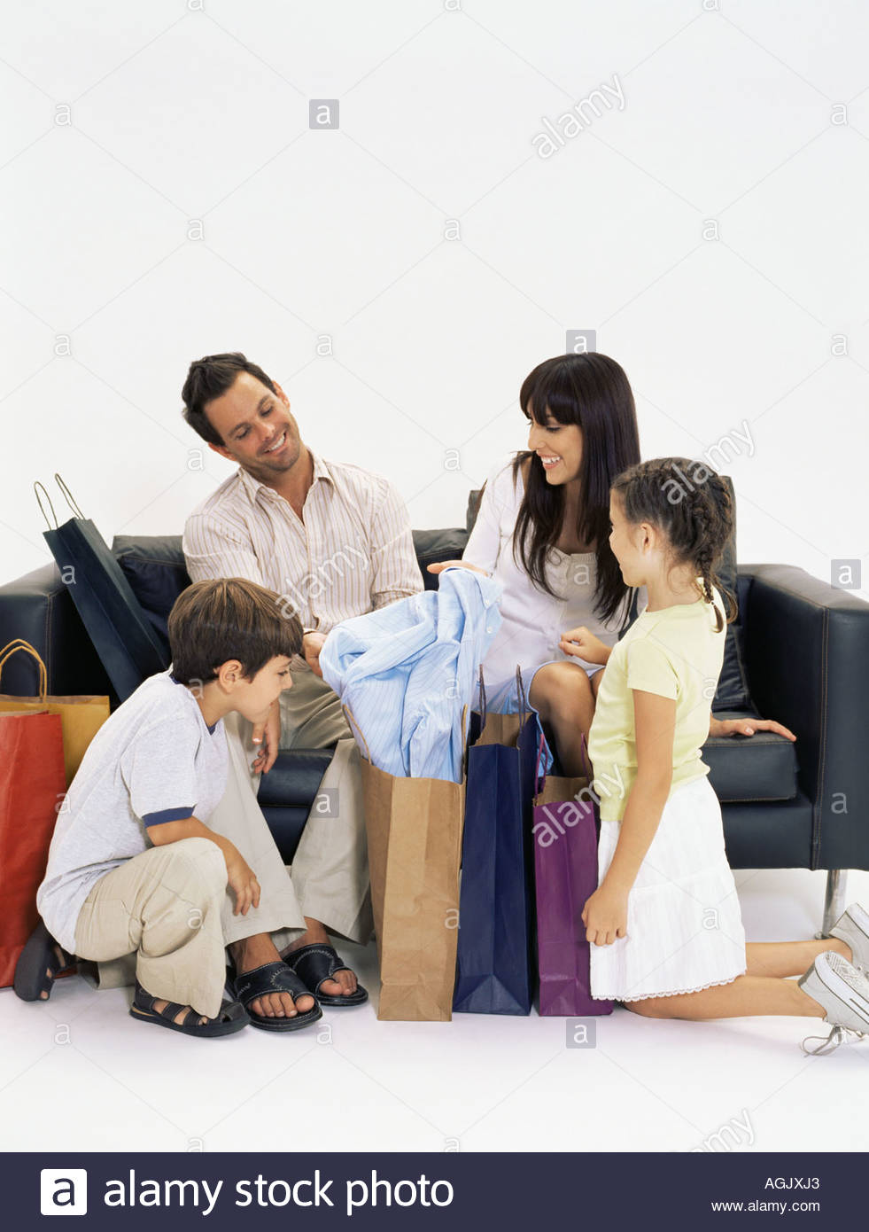 Family looking at clothes mother has bought Stock Photo
