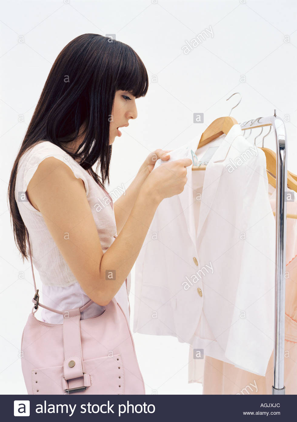 Woman looking at jacket price label - Stock Image