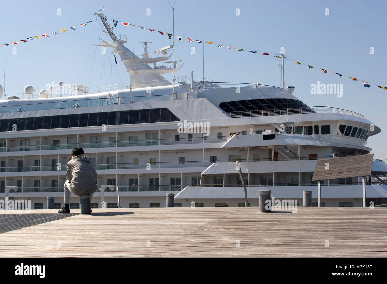 A man watches a cruise ship tied up to the dock in Yokohama, Japan - Stock Image