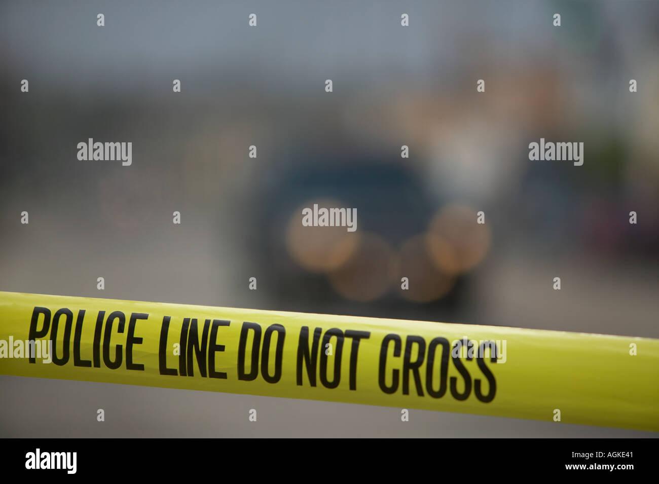 Police line tape blocking urban street - Stock Image