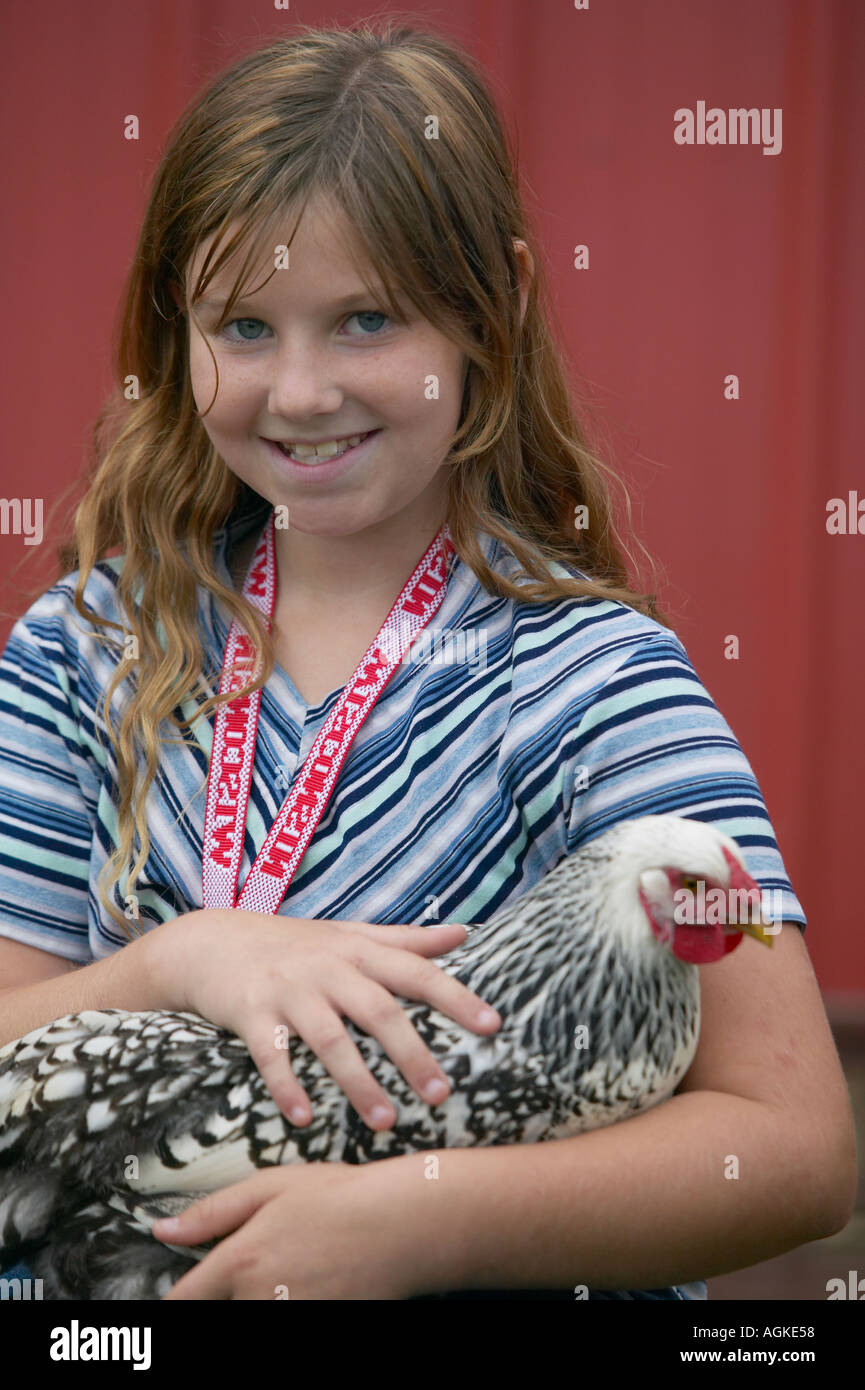 Young girl holding a chicken - Stock Image