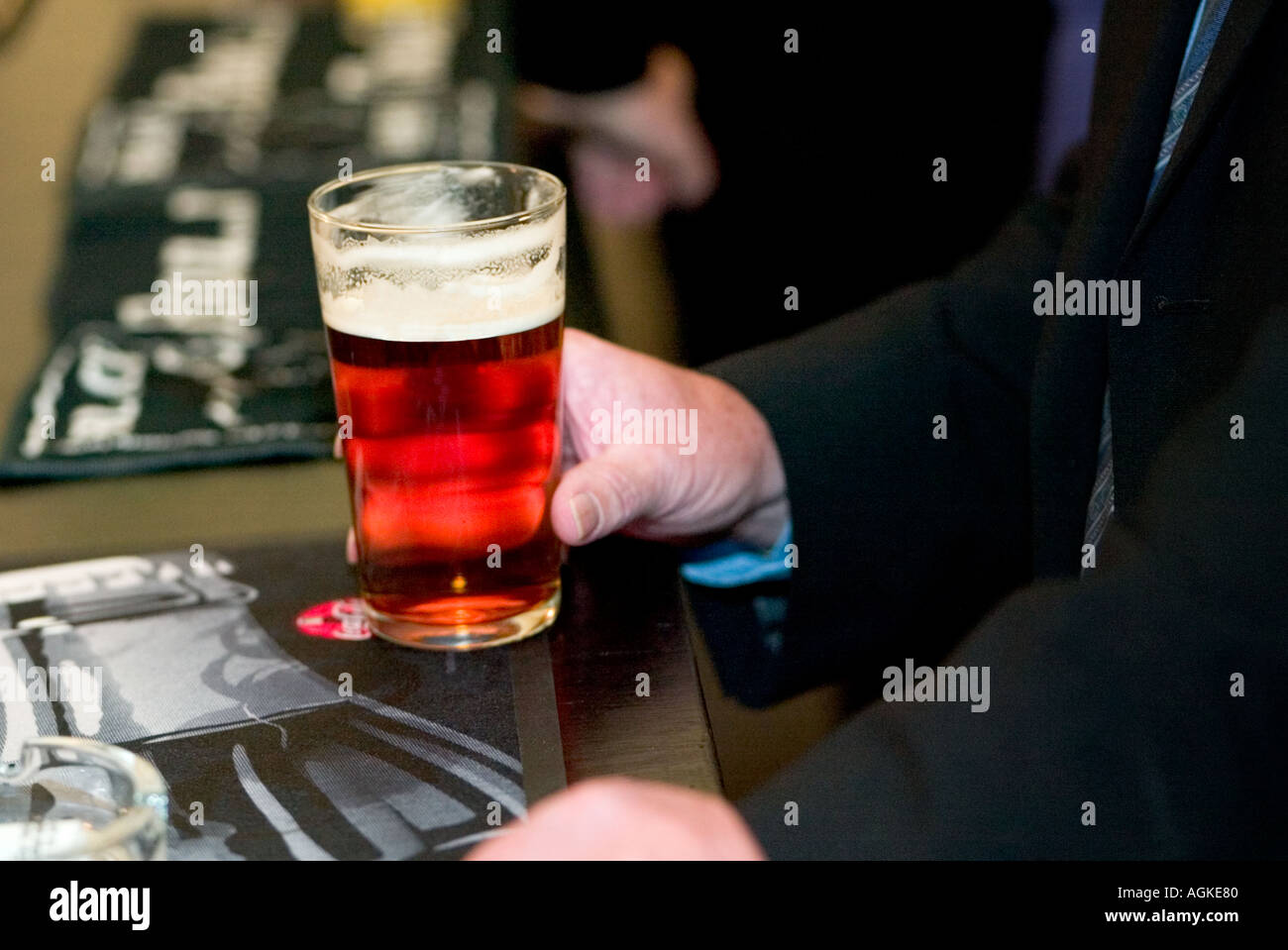 Man holding his pint of beer on a pub bar counter Stock Photo