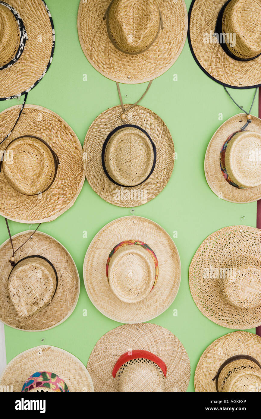 Close-up of straw boater hats hanging on the wall - Stock Image
