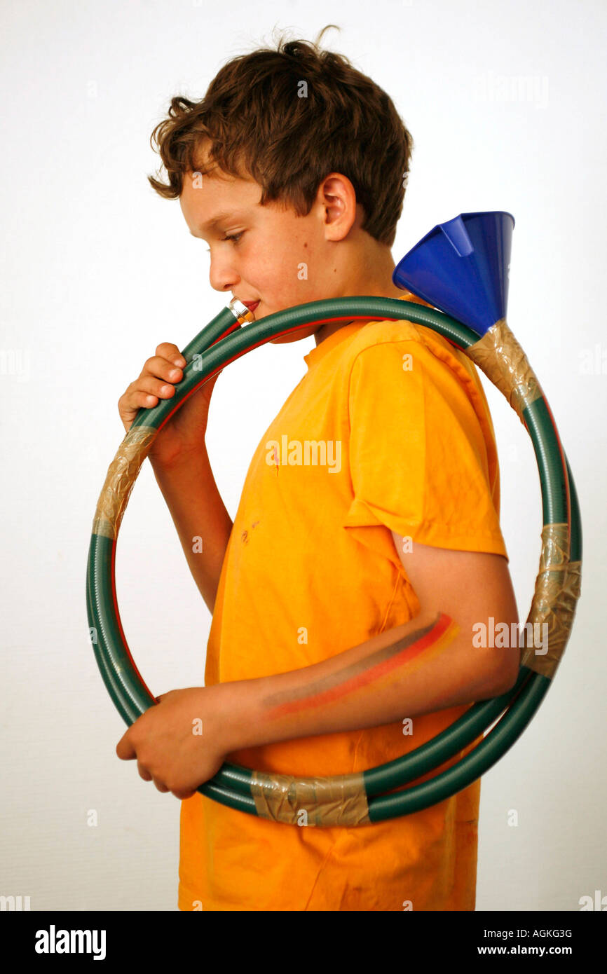 a young boy playing a self made musical instrument - Stock Image