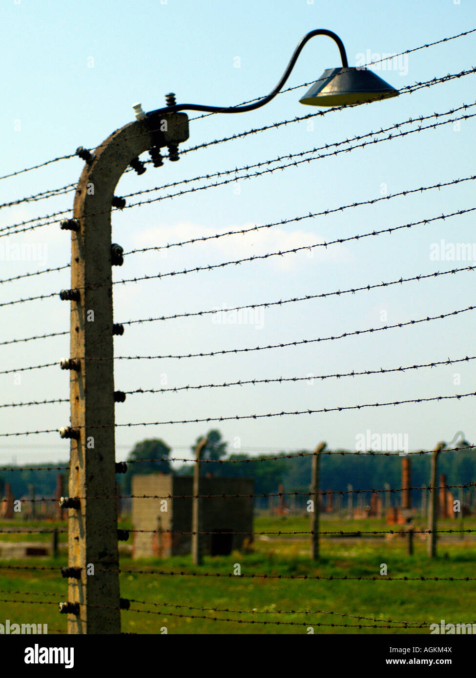 Barbed wire, barracks, and empty fields and ruins at the Auschwitz concentration camp outside of Krakow, Poland. - Stock Image