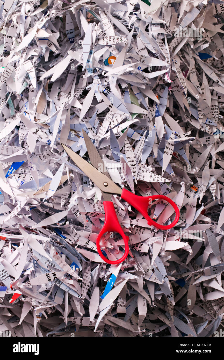Scissors on shredded paper - Stock Image
