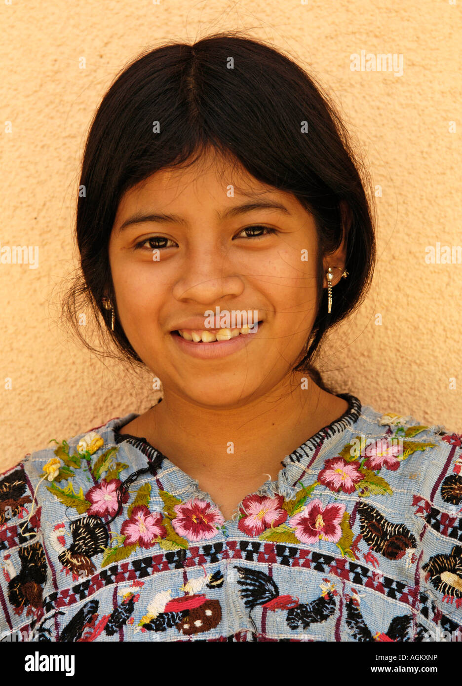 Guatemala, Santiago Atitlan, Portrait of smiling girl against yellow wall. - Stock Image