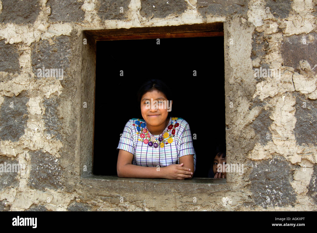 Guatemala, Santiago Atitlan, Portrait of smiling girl in crude window with peeking boy. - Stock Image
