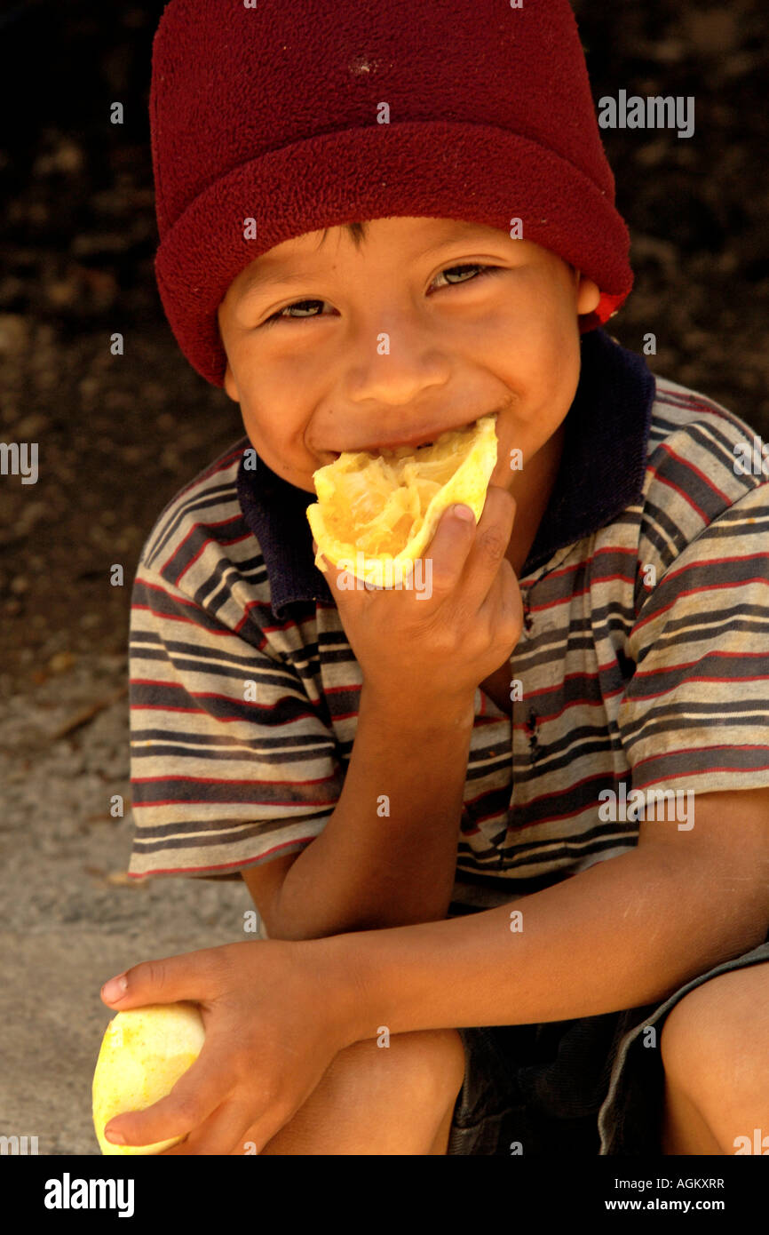 Guatemala, Santiago Atitlan, Portrait of young boy eating orange. - Stock Image