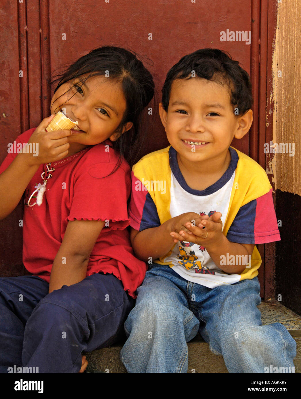 Guatemala,  Santiago Atitlan, Portrait of boy and girl sitting in doorway, one eating ice cream. - Stock Image