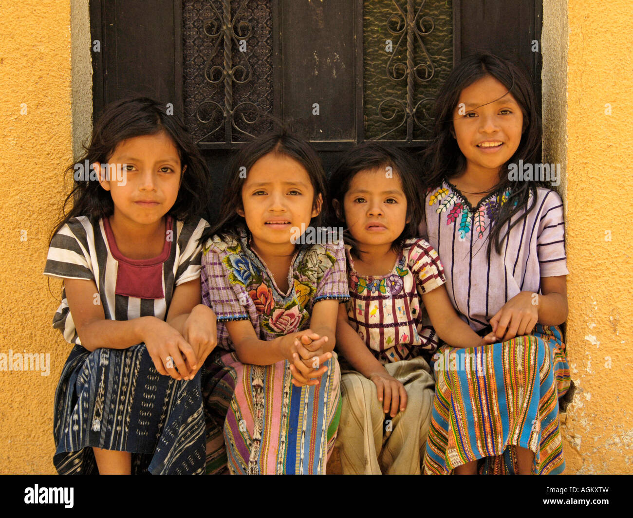Guatemala, Santiago Atitlan, Portrait of four young girls sitting in a doorway. - Stock Image