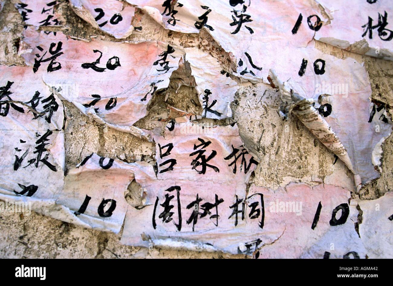 China Yunnan Lijiang old town weathered and torn wall poster - Stock Image