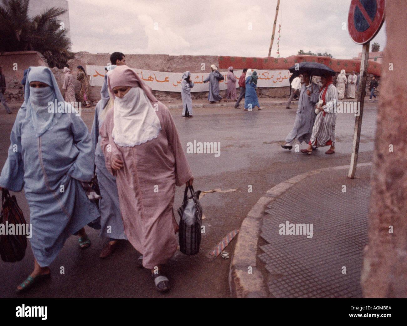 Street scene of yashmak veiled Muslim women in Marrakech Marrakesh in Morocco in the Maghreb in North Africa Sahara. Islamic Islam People Moorish - Stock Image