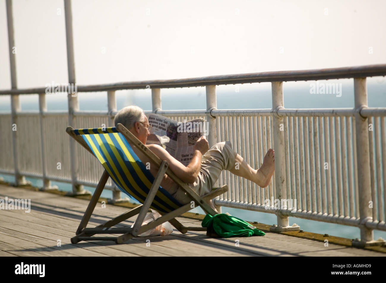 Sun bathing in deck chair on the pier boscomb - Stock Image