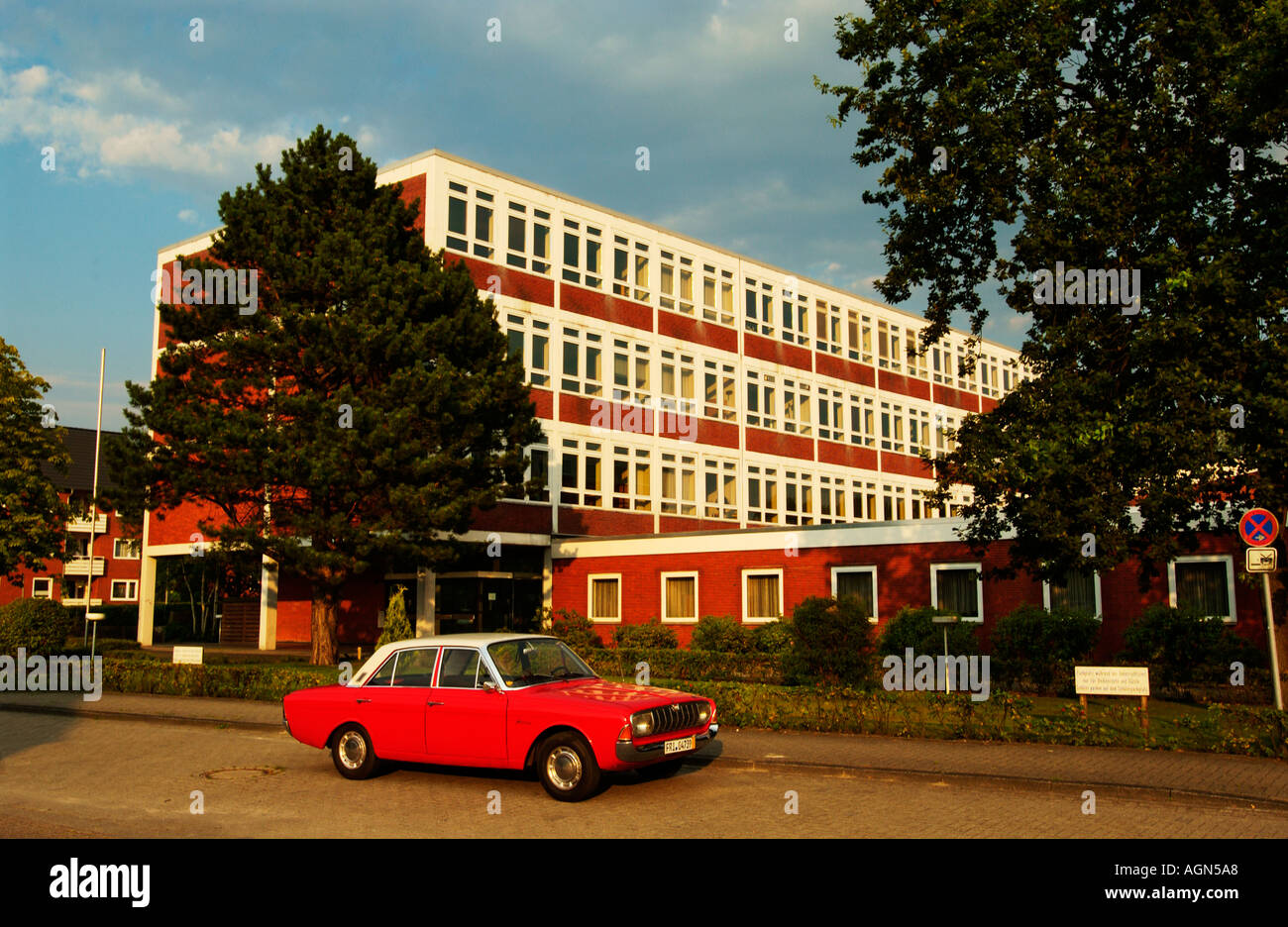 old car rda germany ford seventies red building kitch street - Stock Image