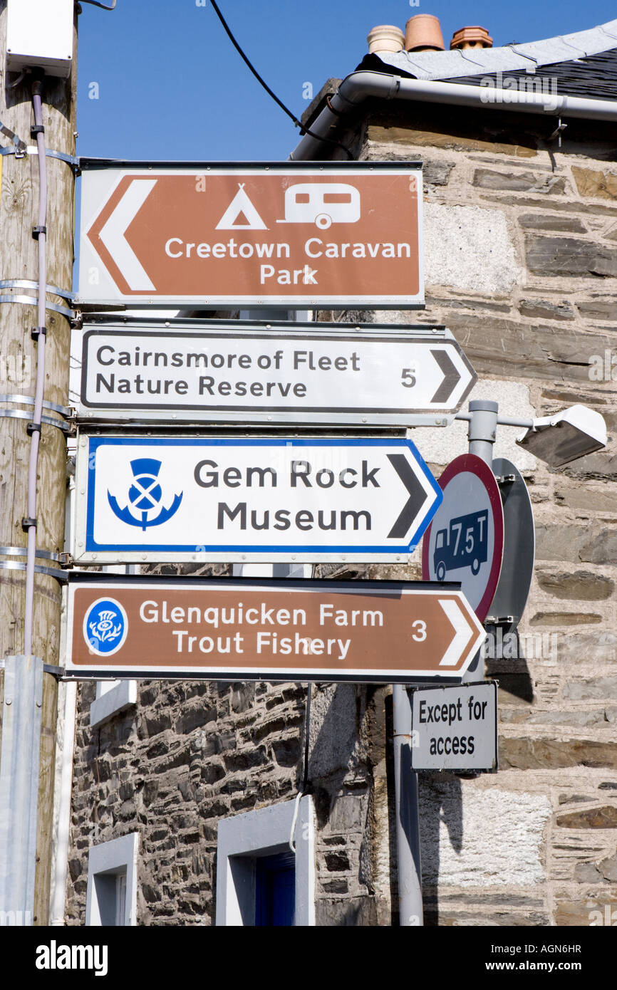 Road traffic signs on lap post pointing tourists to local visitor attractions in Adamson Square in Creetown Galloway - Stock Image