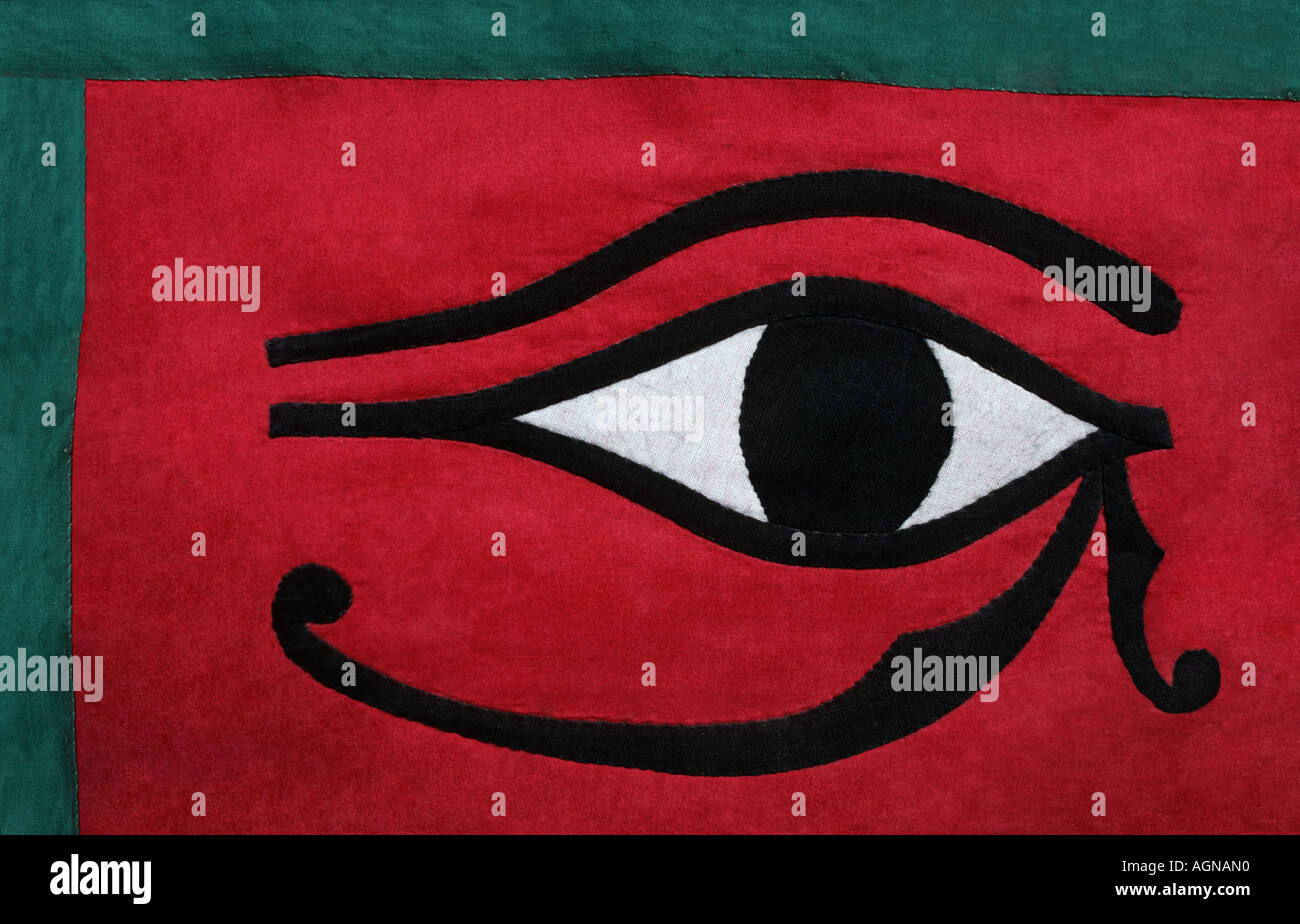 Detail of an applique decorated fabric with the eye of Horus on a red background with green trim Luxor market Egypt - Stock Image