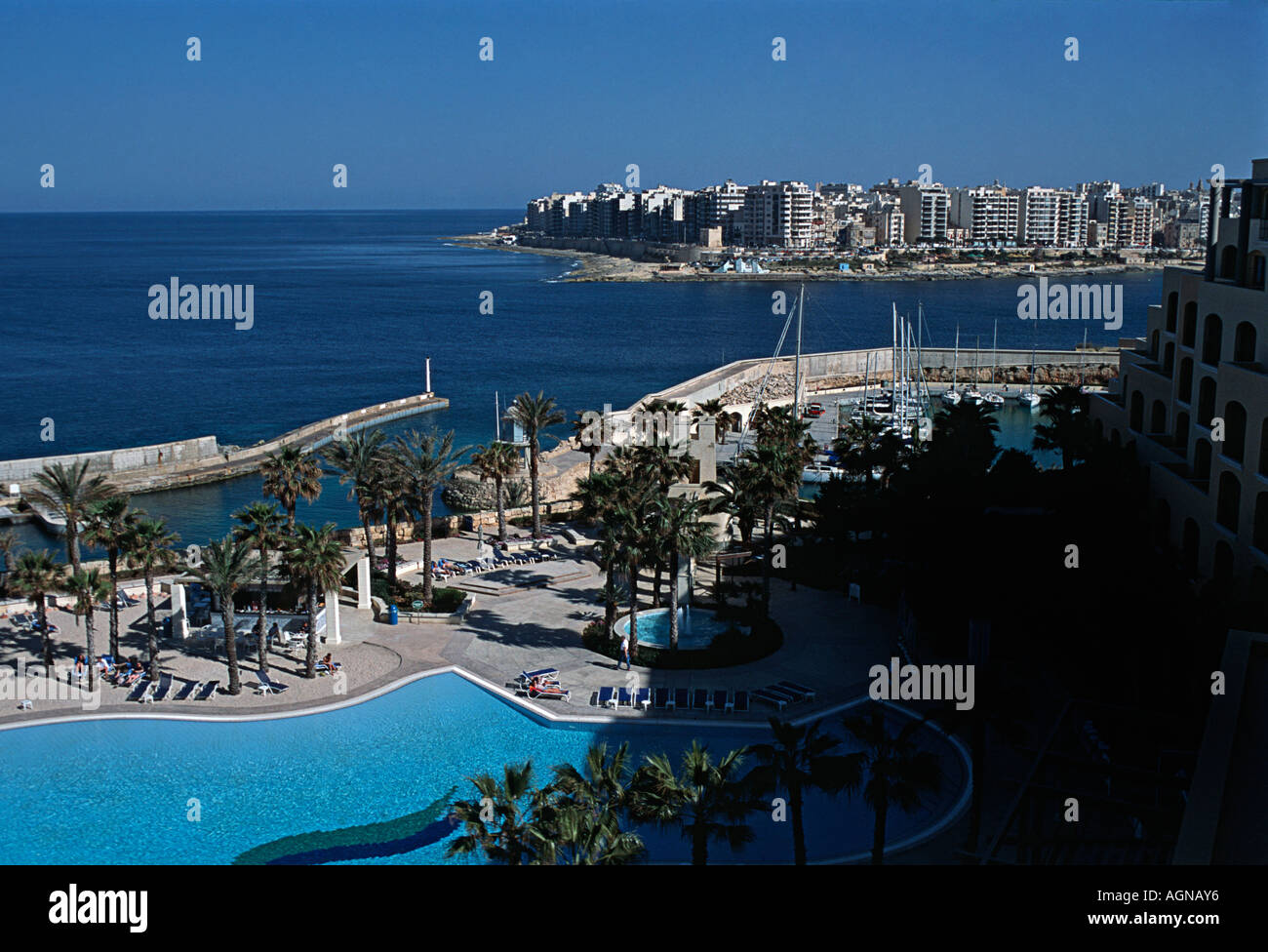The Hilton Hotel Portomaso St Julian s Malta With town and sea beyond the swimming pool MALTA - Stock Image