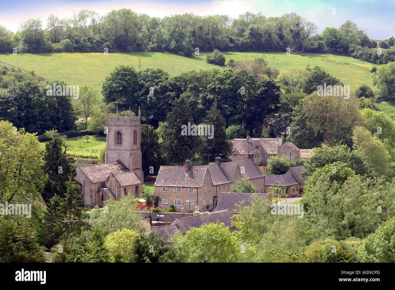 THE VILLAGE OF NAUNTON WITH ST ANDREWS CHURCH GLOUCESTERSHIRE UK - Stock Image