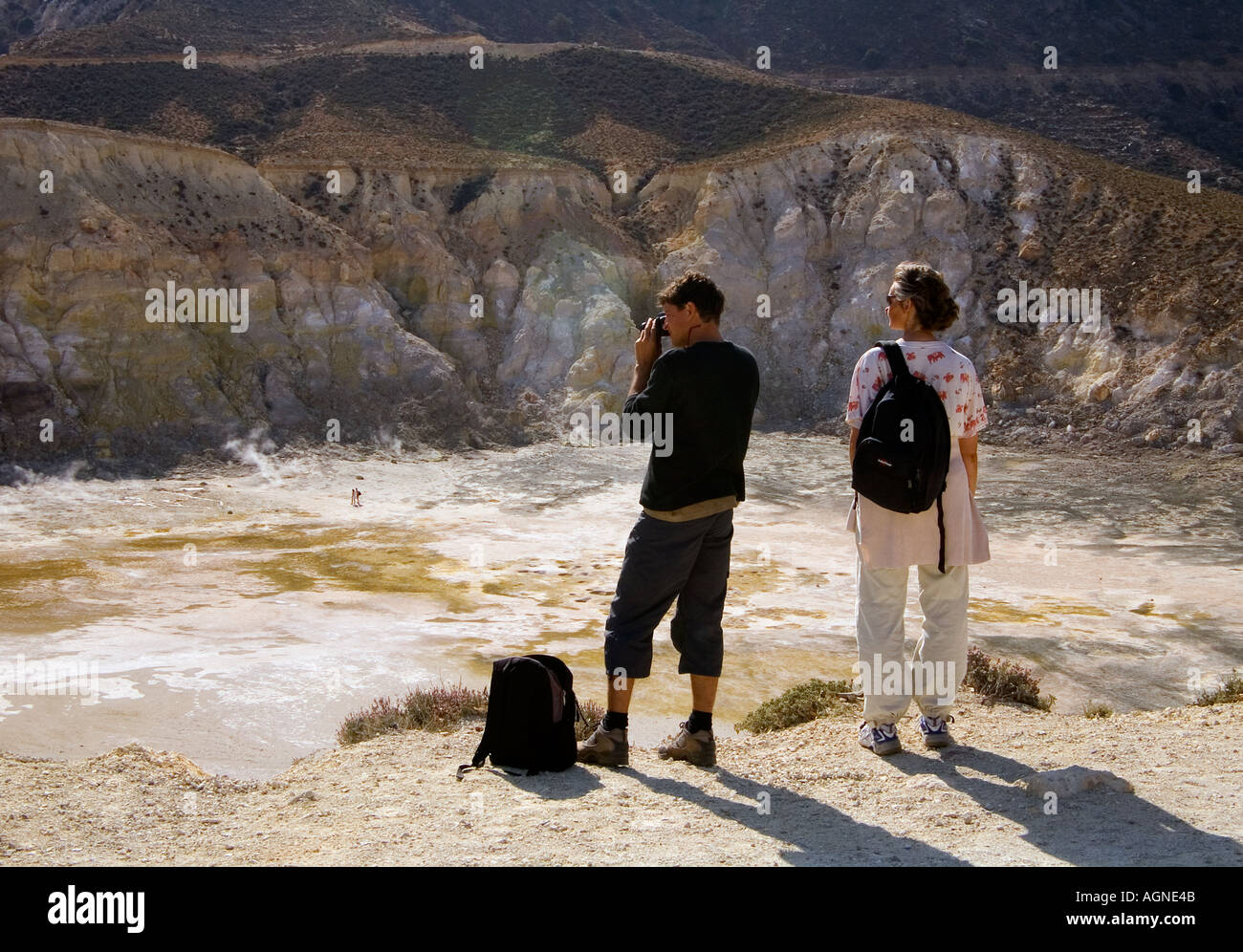 dh Stefanos volcano LAKKI PLATEAU GREECE NISYROS Man and woman couple tourists looking down into semi active volcano - Stock Image