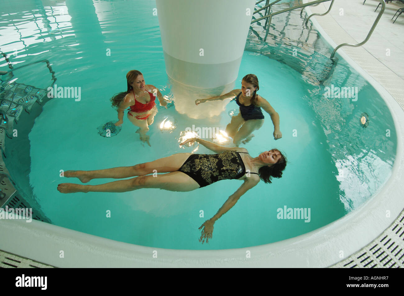 Three young women bathing in a modern pool above the ancient Roman baths of Bath, Somerset. Stock Photo