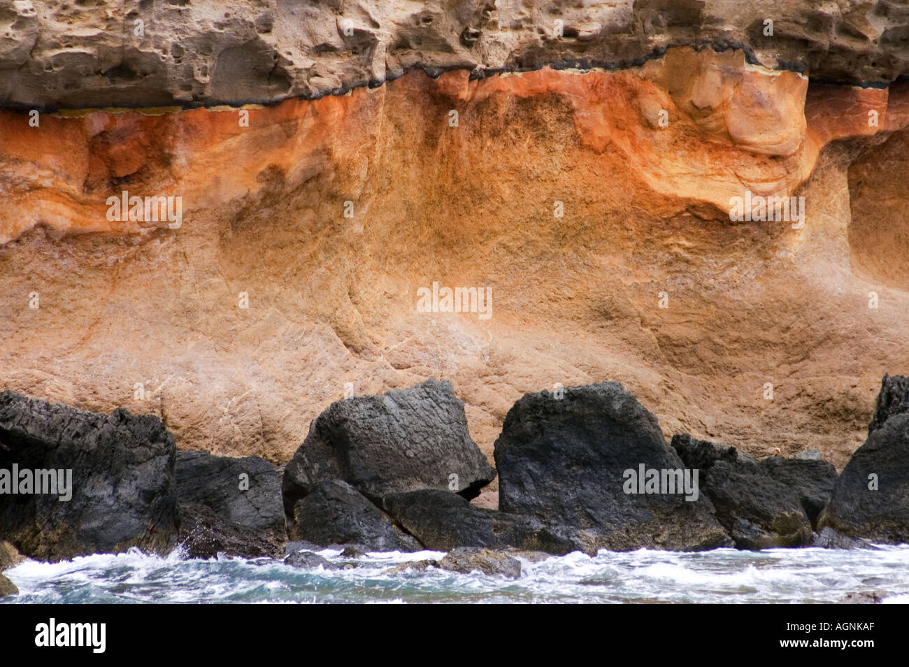 rough shore coast Gran Canaria Canary Islands SPAIN in the south of Gran Canaria near Puerto Mogan  red stone ferric oxide - Stock Image