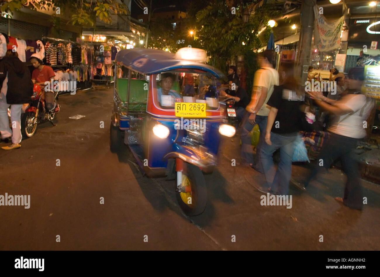 Tuk Tuk passing Th Khao San Road in the evening Banglamphu Bangkok Thailand Stock Photo