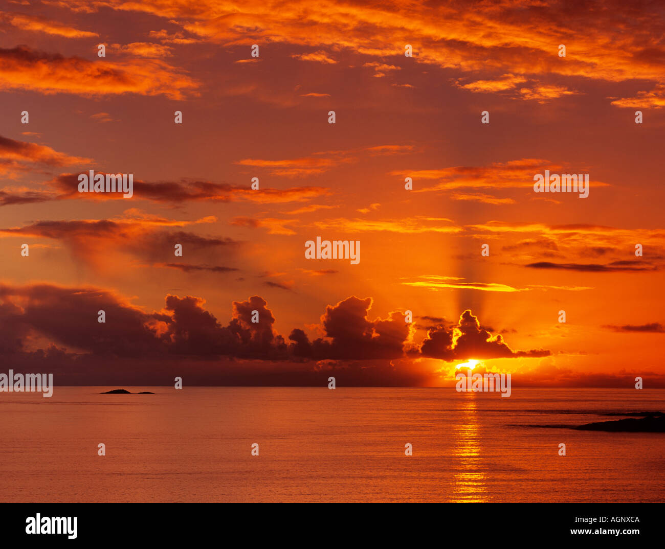 Stunning red sky at sunset with sunbeams through clouds over Firth of Lorn on Scottish west coast at sundown. Argyll & Bute Scotland UK Britain - Stock Image