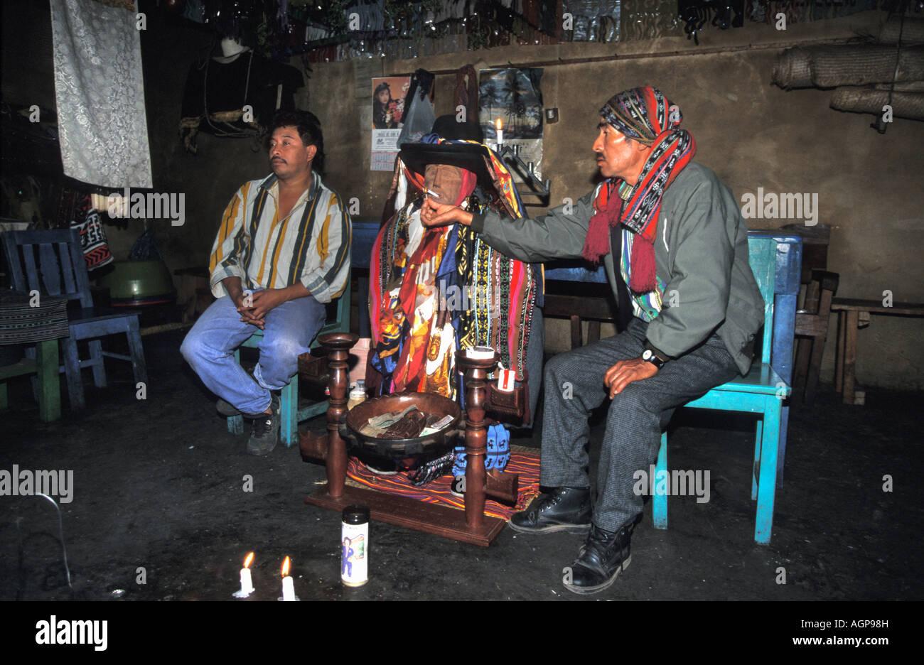 Guatemala Santiago de Atitlan Drunk man giving cigarette to statue representing local god - Stock Image