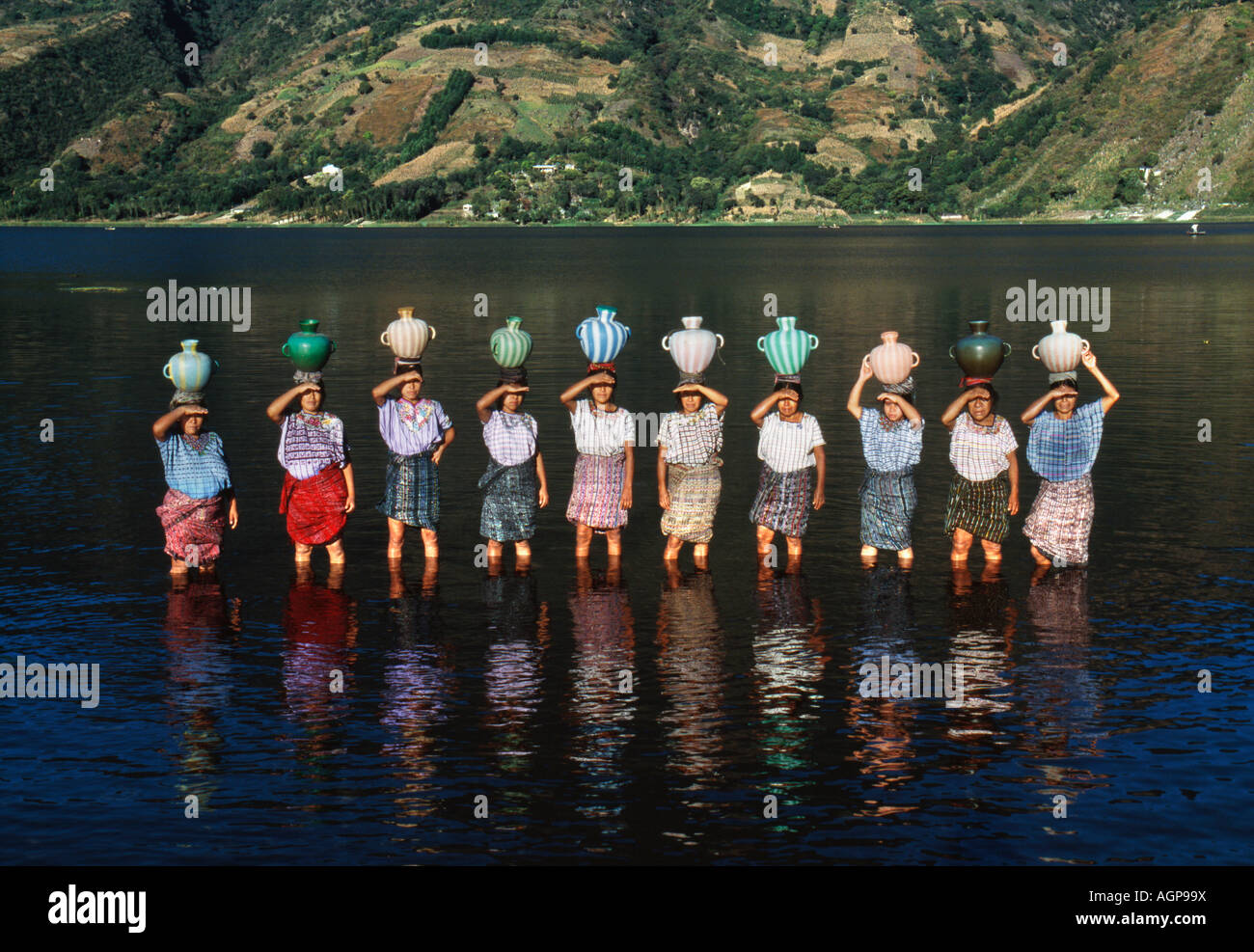 Guatemala Santiago de Atitlan Women carrying pots of water on head - Stock Image