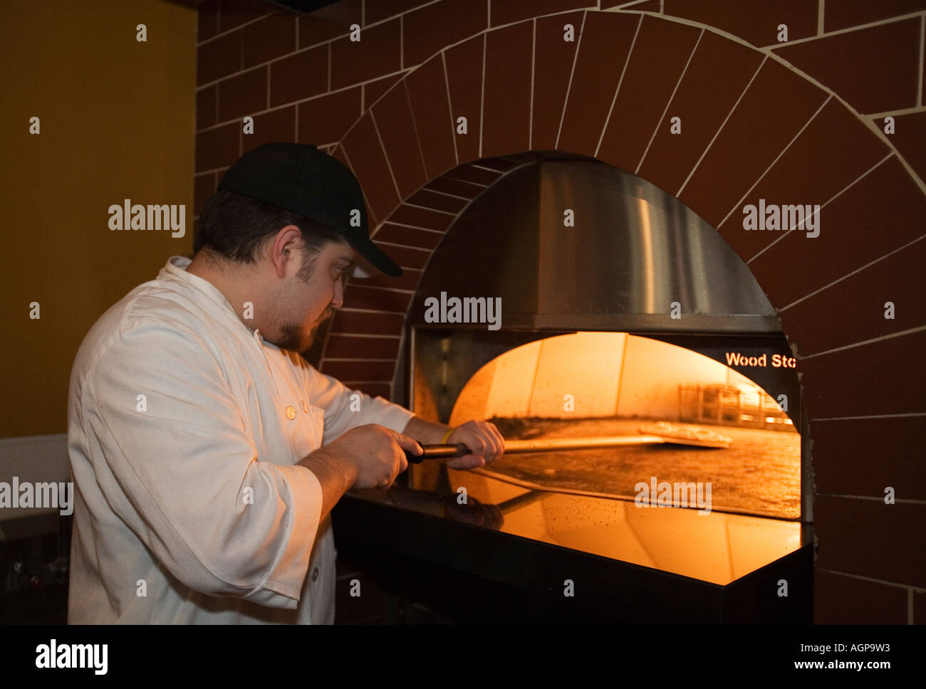 Detroit Michigan Frankie Paulick a line cook at Small Plates restaurant puts a pizza in the oven Stock Photo