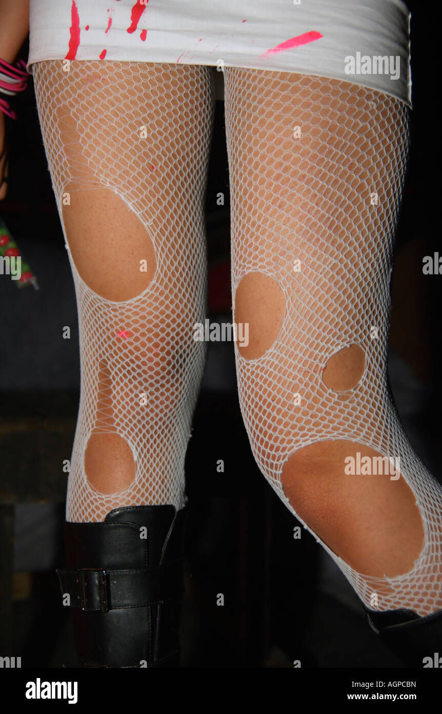 A young female model wearing a dirty skirt and torn fishnet stockings - Stock Image
